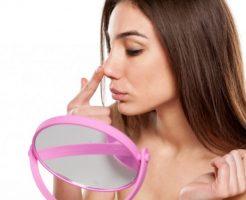 鏡を見ながら鼻を触る女性