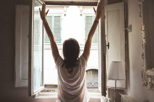 朝窓を開ける女性